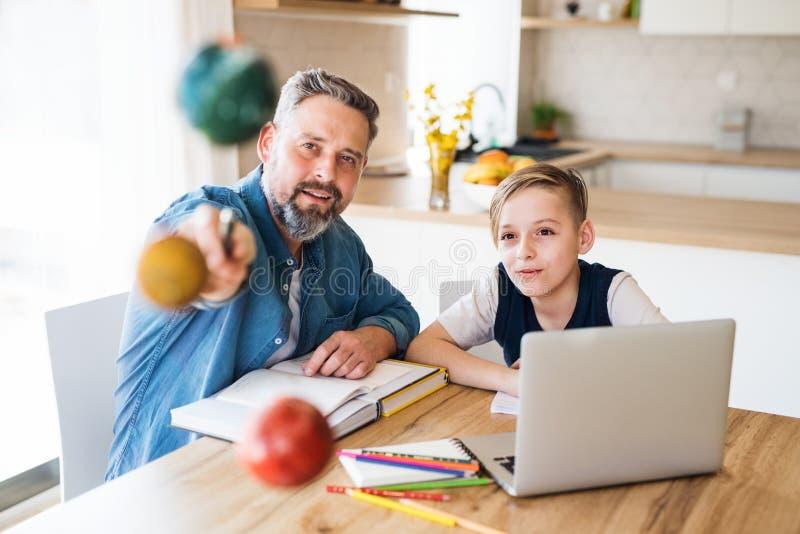 有小儿子的成熟父亲在桌上户内,工作坐学校项目 免版税库存图片