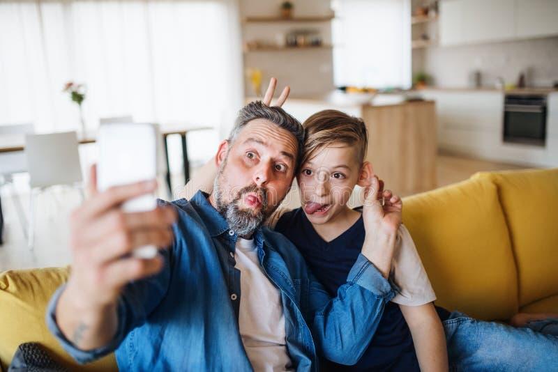 有小儿子的父亲坐沙发户内,做鬼脸,当采取selfie时 库存图片