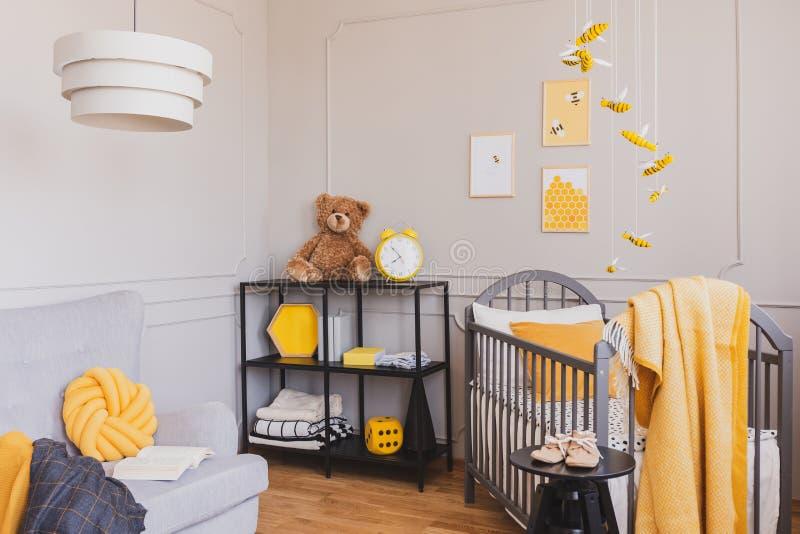 有小儿床和工业黑金属架子的时髦的灰色和黄色婴孩卧室 库存照片