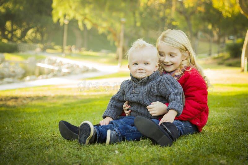 有小兄弟佩带的外套的小女孩在公园 免版税库存照片