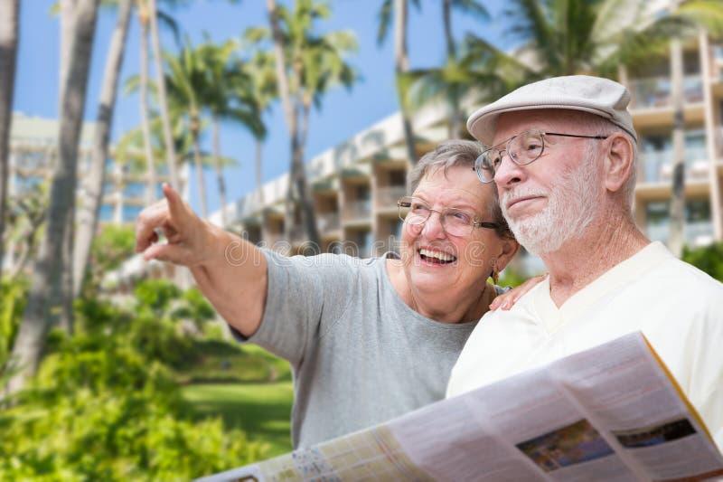 有小册子的愉快的资深成人夫妇游人 免版税库存照片