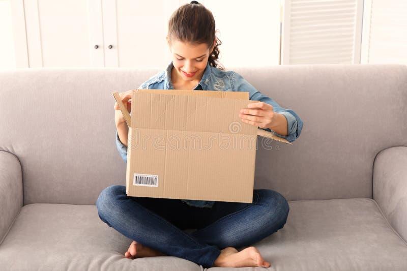 有小包的美丽的少妇开头箱子,当在家时坐沙发 免版税库存照片