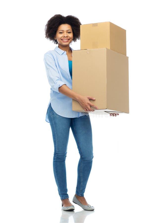 有小包箱子的愉快的非洲少妇 库存图片