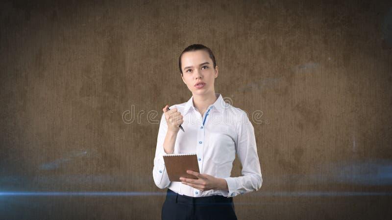 有小圆面包文字的专业确信的女实业家在演播室背景隔绝的她的组织者 到达天空的企业概念金黄回归键所有权 库存照片