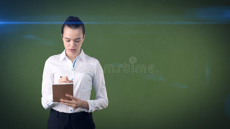 有小圆面包文字的专业确信的女实业家在演播室背景隔绝的她的组织者 到达天空的企业概念金黄回归键所有权 免版税库存图片