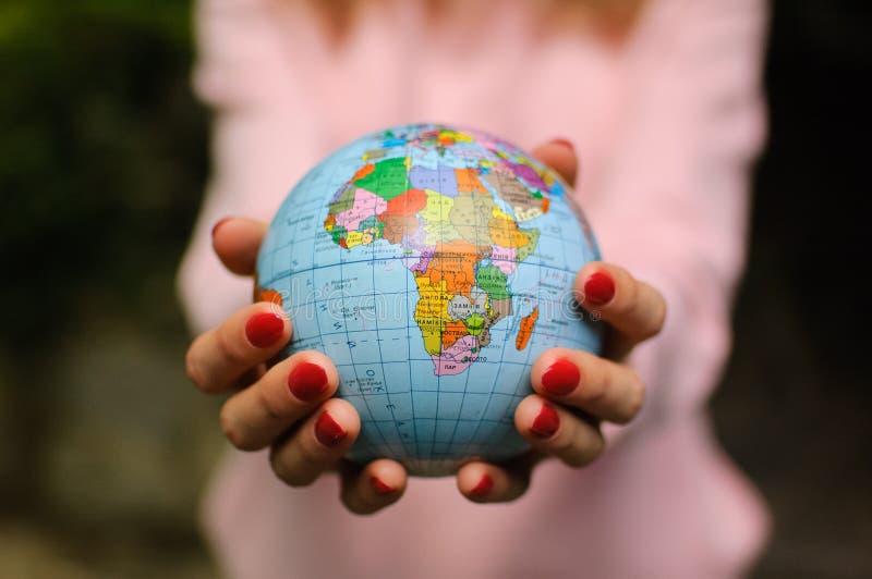 有小地球的女性手与乌克兰名字和斯拉夫语字母的信件对此 非洲大陆是可看见的 ?? 免版税库存照片