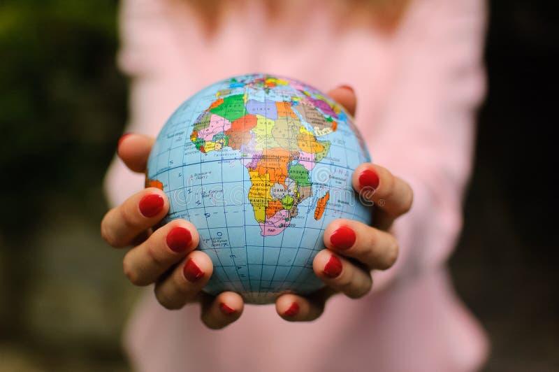 有小地球的女性手与乌克兰名字和斯拉夫语字母的信件对此 非洲大陆是可看见的 ?? 库存图片