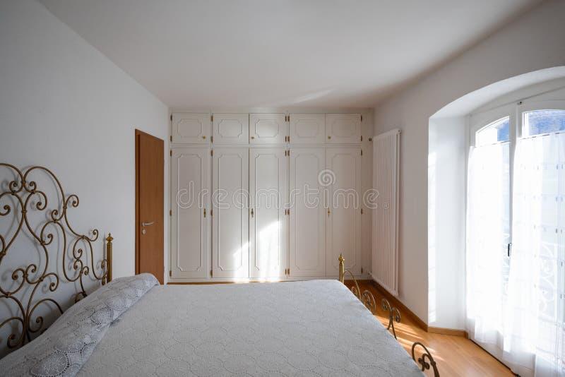 有小垫布盖子的主卧室 免版税库存照片