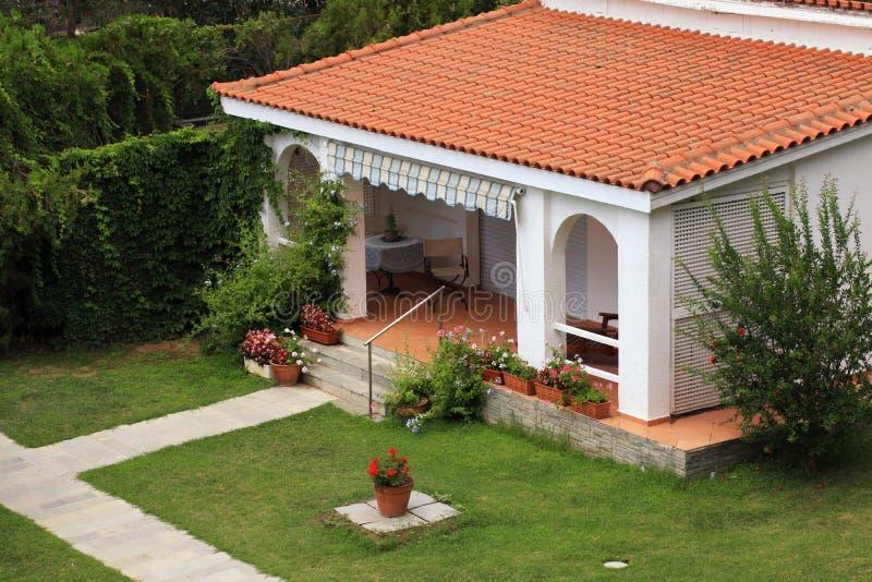 有小大阳台的美丽的白色房子在庭院里。 免版税库存照片