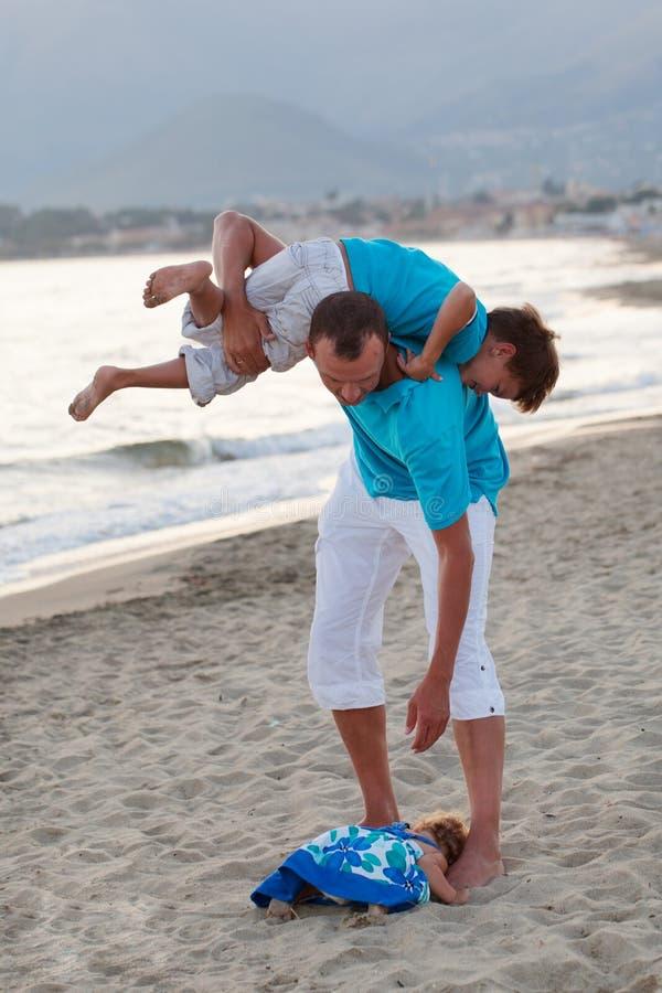 有小女儿儿子的愉快的年轻父亲户外 免版税库存图片