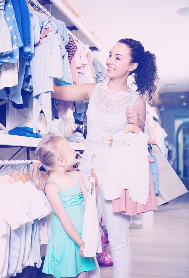 有小女儿女孩买的衣裳的母亲 免版税库存图片