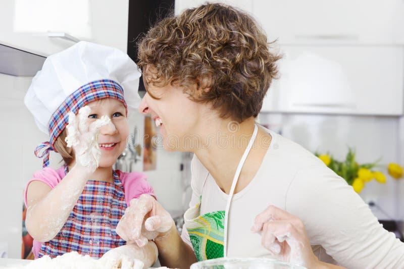 有女儿快乐烹调的母亲 库存图片