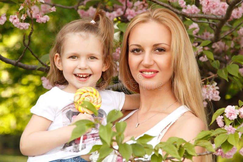 有小女儿的愉快的母亲舔糖果春天公园outdoo 图库摄影