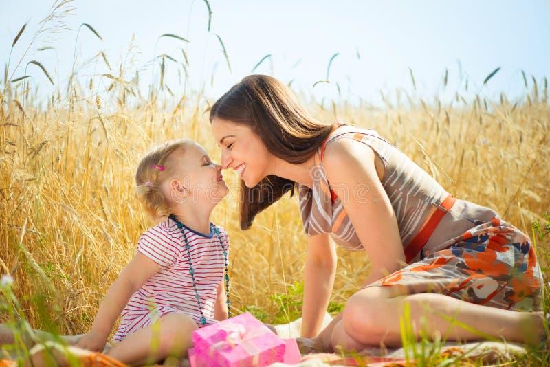 有小女儿的愉快的年轻母亲领域的在夏日 库存图片