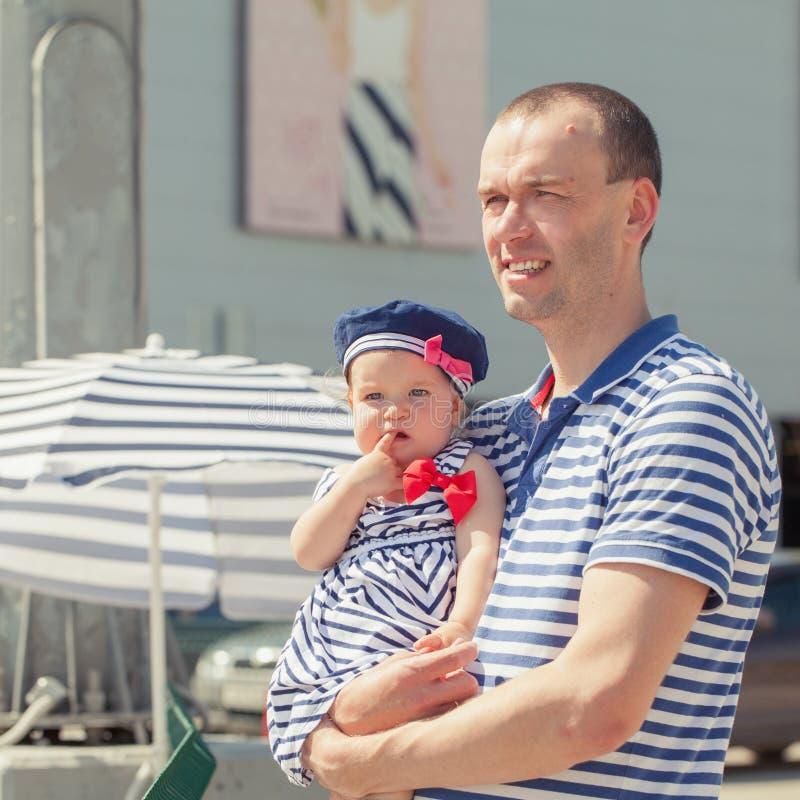 有小女儿的愉快的年轻父亲户外 库存照片
