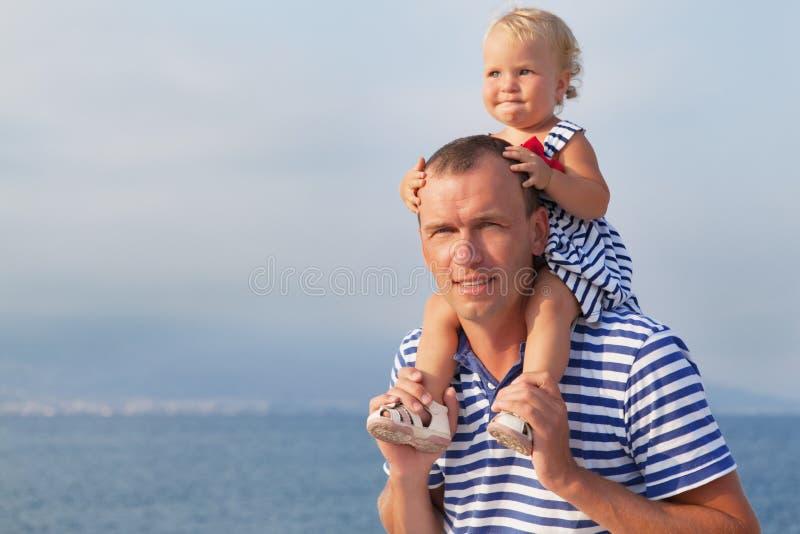 有小女儿的愉快的年轻父亲户外 免版税库存图片