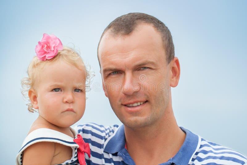 有小女儿的愉快的年轻父亲户外 免版税库存照片