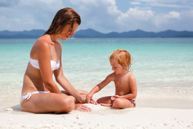 有小女儿的母亲海滩的 库存图片