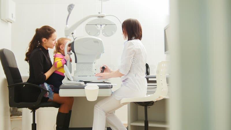 有小女儿的母亲眼科的-儿童眼科学-验光师检查儿童` s眼睛 免版税库存照片