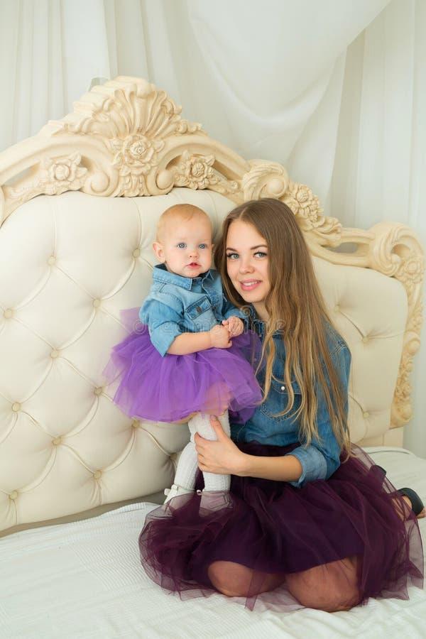 有小女儿的美丽的愉快的母亲 免版税图库摄影