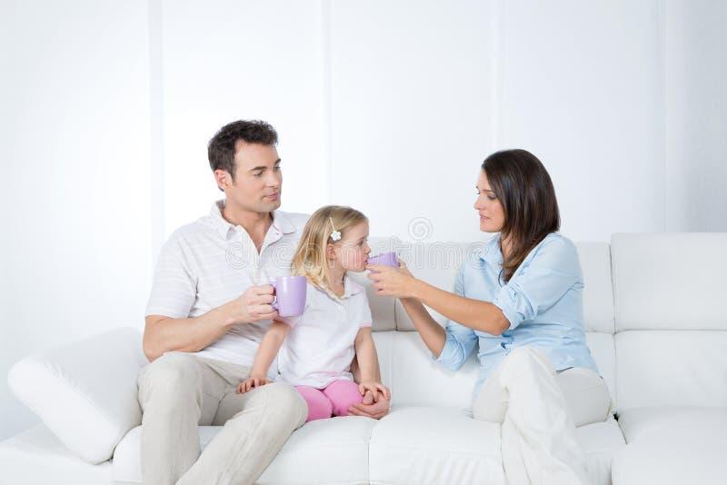 有小女儿的仔细的父母 库存照片