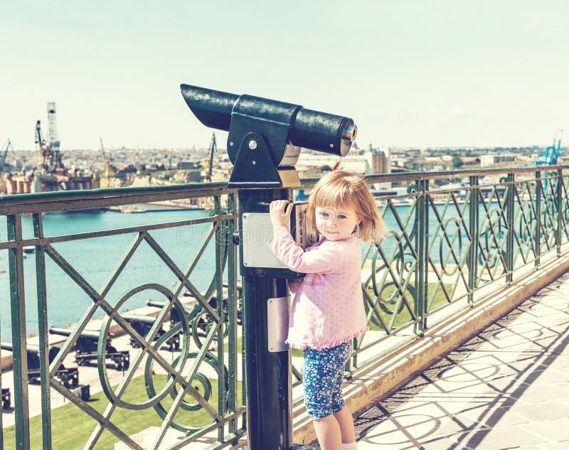 有小女孩和望远镜的观察台 免版税库存照片