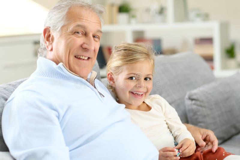 有小女孩的微笑的祖父沙发的 免版税库存照片