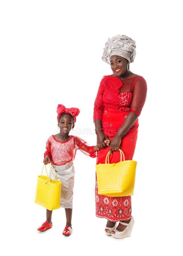 有小女孩的美丽的非洲妇女传统红色衣物的 免版税库存照片