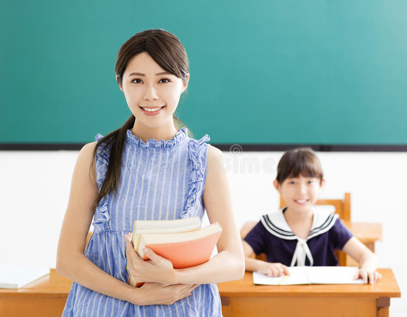 有小女孩的年轻老师在教室 库存照片
