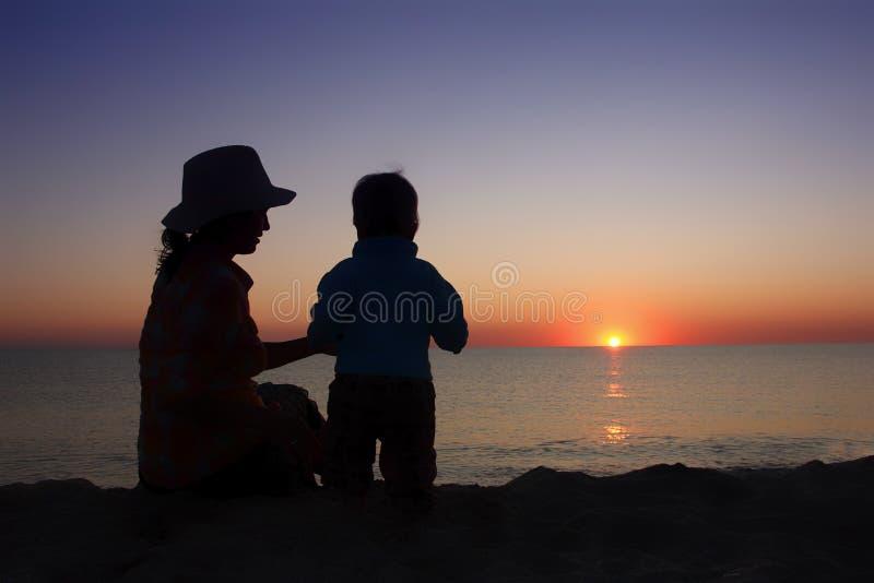 有小婴孩的母亲一起坐日落海滩 家庭 库存图片