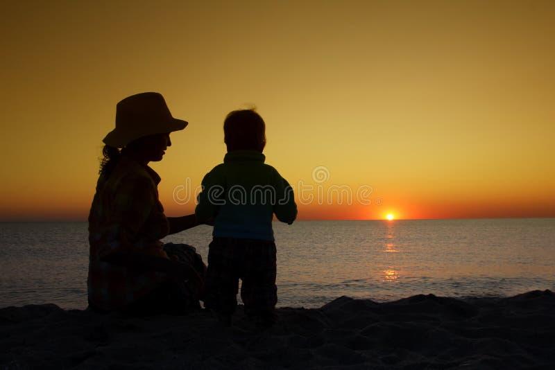 有小婴孩的母亲一起坐日落海滩 家庭 免版税库存照片
