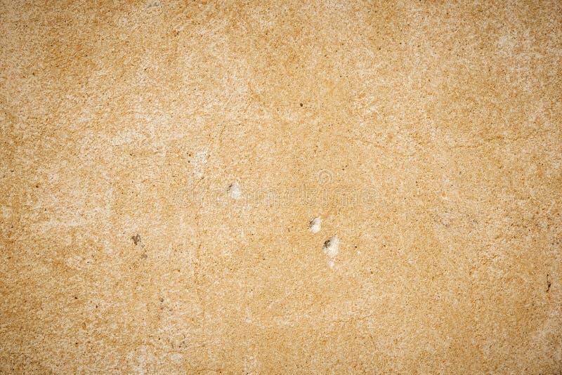 有小孔的老米黄墙壁在墙壁 免版税库存照片
