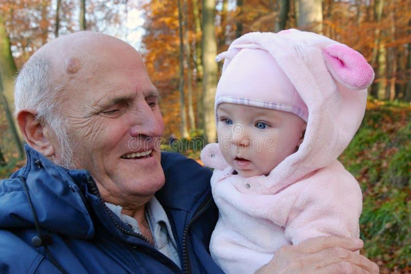 有小孙女的愉快的祖父户外 图库摄影