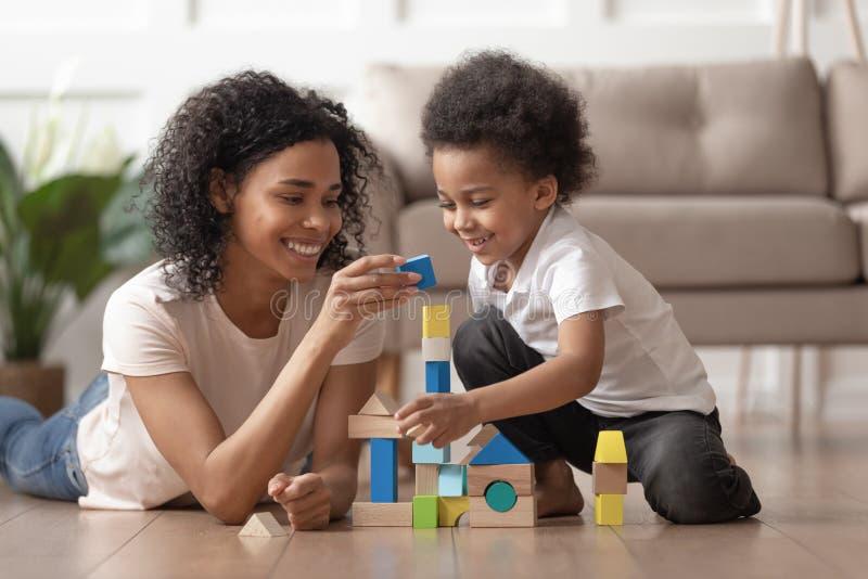 有小孩儿子戏剧的非洲母亲与木块 免版税库存图片
