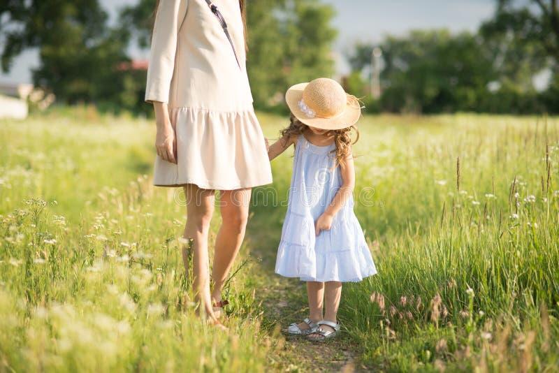 有小孩女孩走的时髦的年轻母亲 库存图片