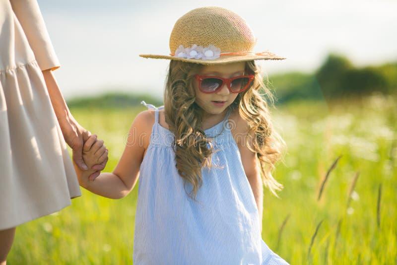 有小孩女孩走的时髦的年轻母亲 免版税库存照片