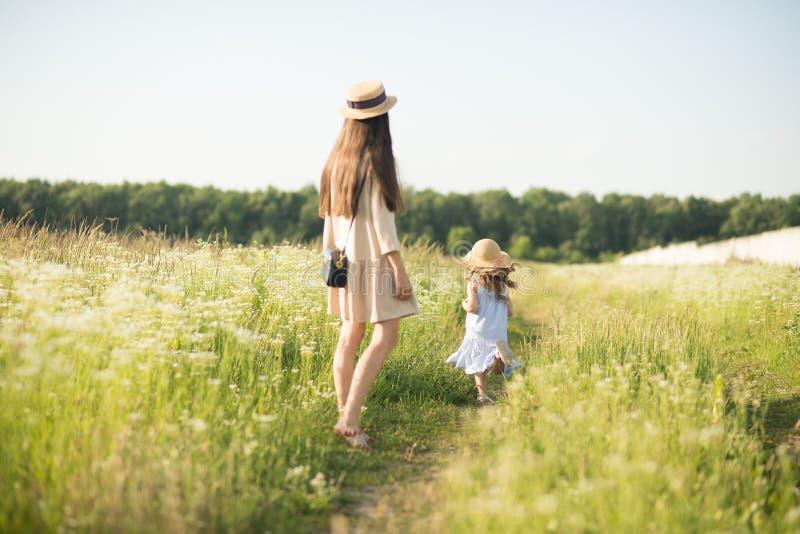 有小孩女孩走的时髦的年轻母亲 库存照片