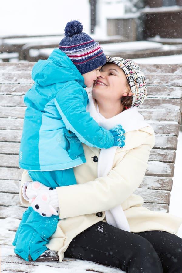 有小孩男孩的年轻母亲坐长凳在冬天公园 使用和拥抱与逗人喜爱的小儿子的妇女 免版税库存图片