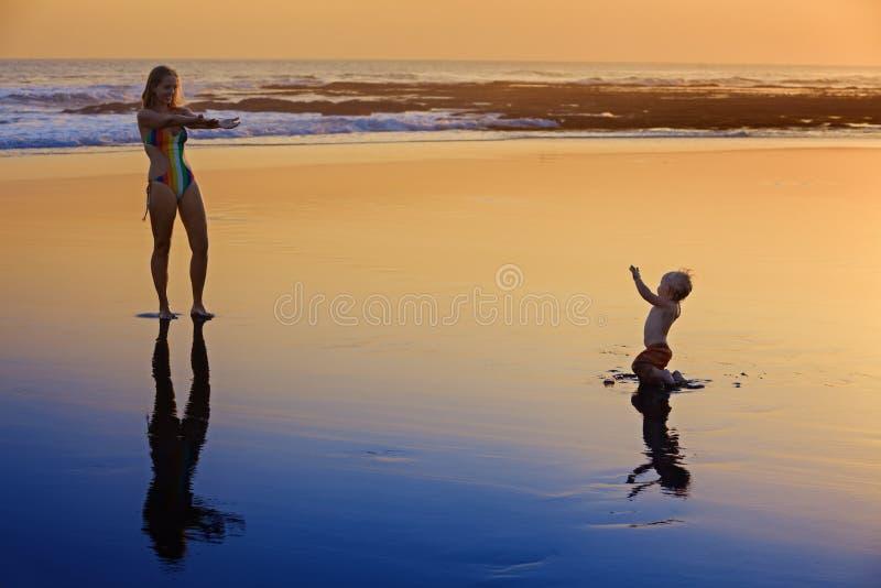 有小孩的母亲日落海海滩的 免版税库存照片