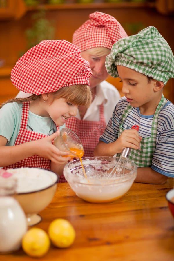 有小孩的祖母在厨房里 免版税库存照片