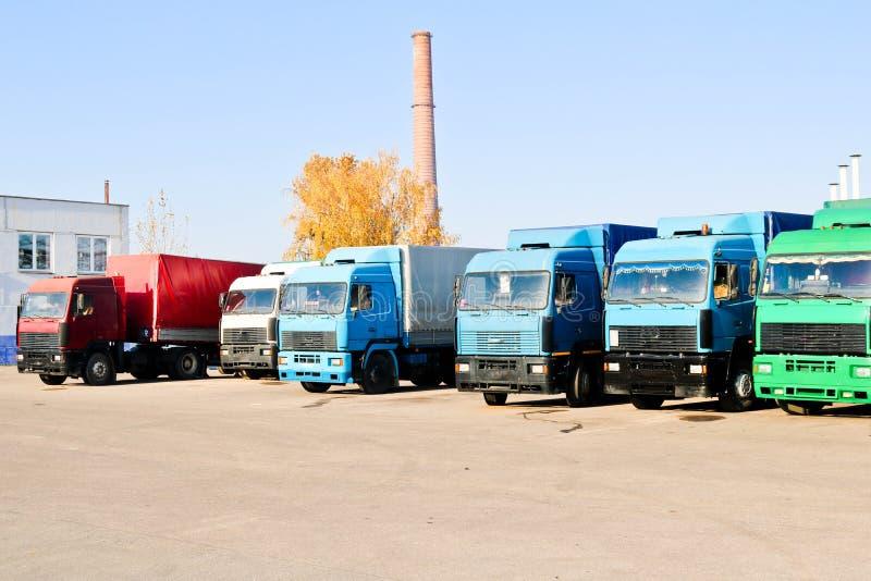 有小室和拖车的大重的货物卡车连续站立准备好货物交付在工业精炼厂 库存照片