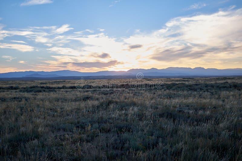 有小山的平静的草原在距离 库存图片