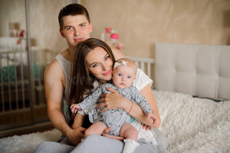 有小心地拿着新出生的bab的父亲的愉快和年轻母亲 库存照片