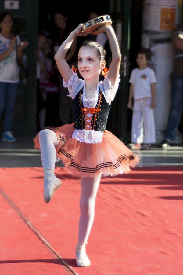 有小手鼓跳舞的年轻芭蕾舞女演员在公开阶段 图库摄影