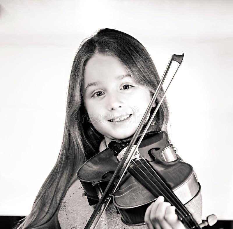 有小提琴、音乐和教育概念的逗人喜爱的女孩,在白色 免版税图库摄影