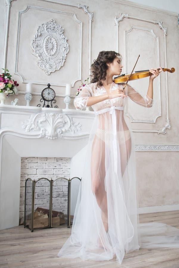 有小提琴的妇女在白色peignoir 被限制的 诱人 免版税库存图片