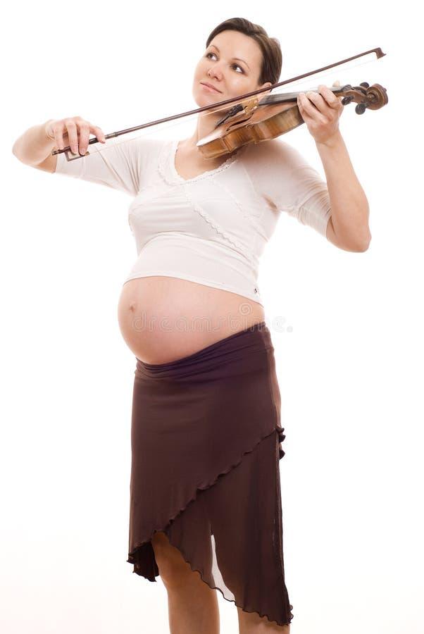 有小提琴的美丽的新孕妇 免版税库存照片