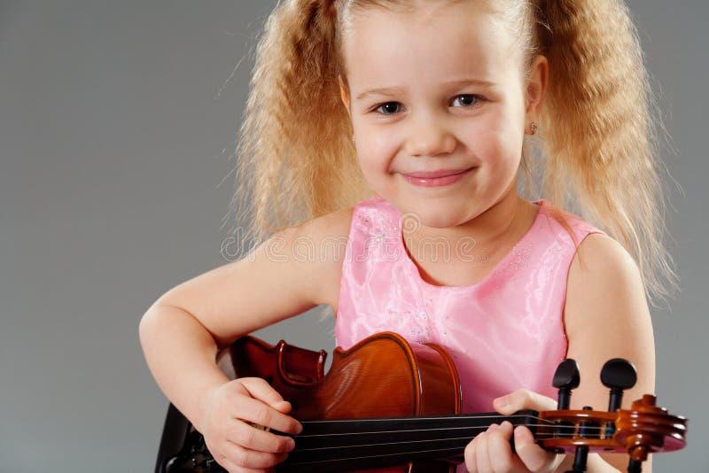 有小提琴的可爱的小女孩 库存图片