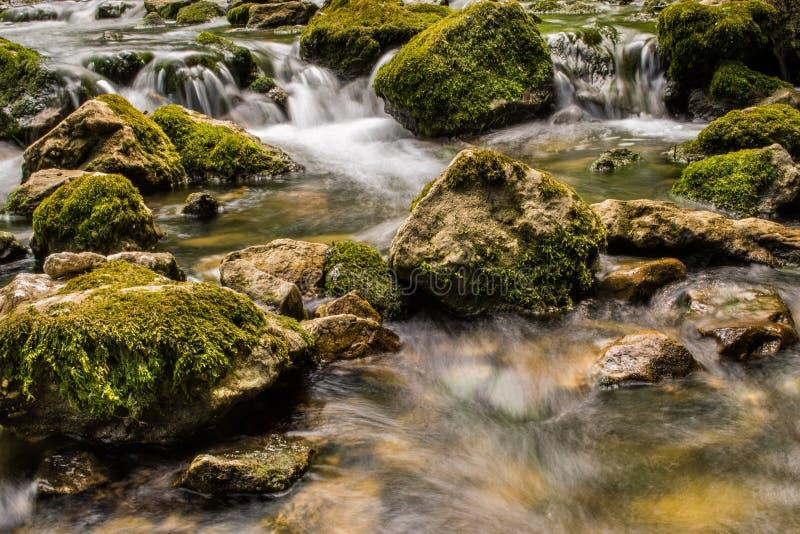 有小瀑布和巨大的岩石的山河 库存照片
