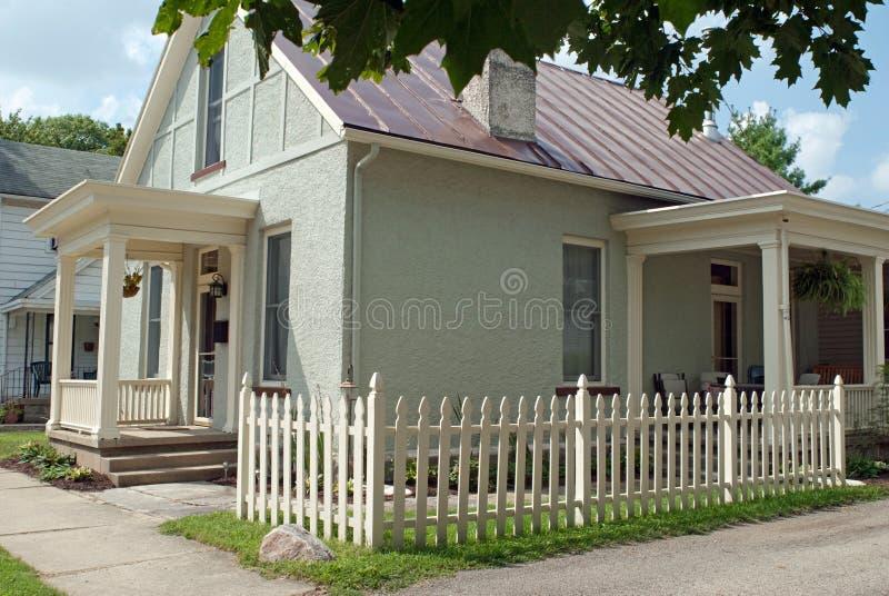有小灰泥村庄的壁角尖桩篱栅 免版税库存照片
